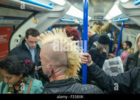A man with a mohican haircut on a tube train underground in London Britain - Stock Photo