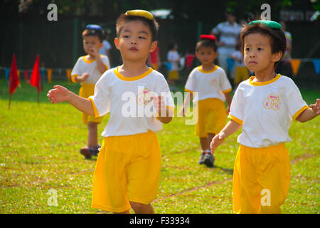 Kindergarten children competing in balancing bean bag race at their sport day. - Stock Photo
