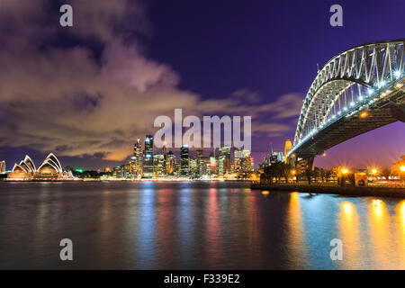 Sydney city CBD in Australia as twilight from across the Harbour with Bridge and skyscrapers landmarks - Stock Photo