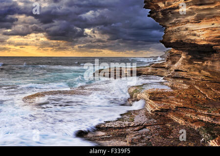 pacific ocean endless waves undermining sandstone rocks of Australian coast near Sydney during stormy sunrise - Stock Photo