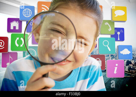 Composite image of cute little girl looking through magnifying glass - Stock Photo