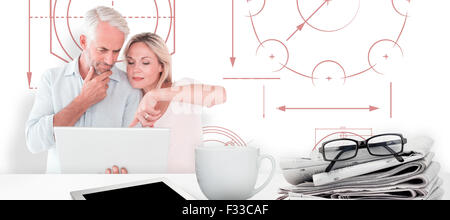 Composite image of mature students using laptop - Stock Photo