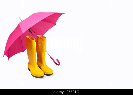 Yellow rubber boots and pink umbrella isolated - Stock Photo