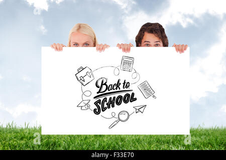 Composite image of happy couple hiding behind a whiteboard - Stock Photo