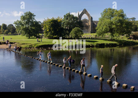 Families risk falling in the River Wharfedale while walking over the stepping stones at Augustinian Bolton Priory, - Stock Photo