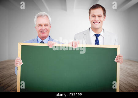 Composite image of smiling tradesmen holding blank sign - Stock Photo
