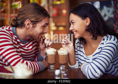 Happy young dates having latte during rest in cafe - Stock Photo