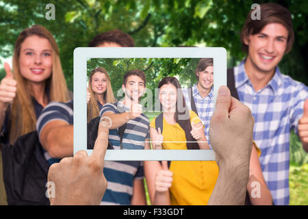 Composite image of hand holding tablet pc - Stock Photo