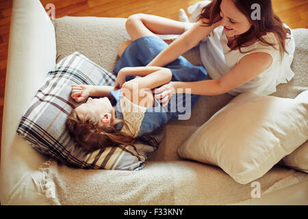 Happy woman and her daughter having fun on sofa - Stock Photo