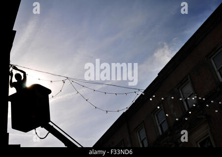 As the town basks in warm Autumnal sunshine Bolton Council put up their Christmas, lights. - Stock Photo