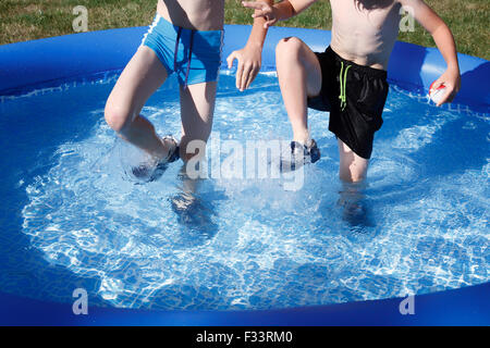 Two young boys outdoors playing in inflatable pool. - Stock Photo