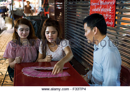 Tarot reader, fortune teller in Bangkok Thailand giving a reading in Yaowarat road at night in central Chinatown - Stock Photo