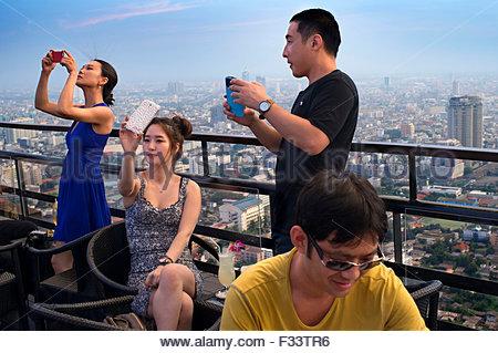 Asian people taking pictures, Banyan Tree Rooftop Vertigo & Moon Bar, Restaurant, Bangkok - Stock Photo