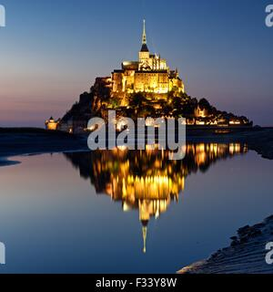 A colour image of reflections of Mont Saint Michel lit up at dusk in a water pool on the beach at Mont Saint Michel - Stock Photo