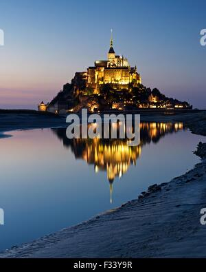 A colour image of reflections of Mont Saint Michel lit up at dusk in a water pool on the beach at Mont Saint Michel
