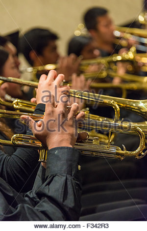 An orchestra of musicians playing trumpet. Musicians in black dress playing golden color trumpets. - Stock Photo