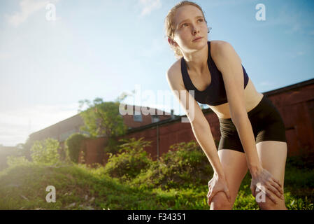 A young athlete takes a break from training outside. - Stock Photo