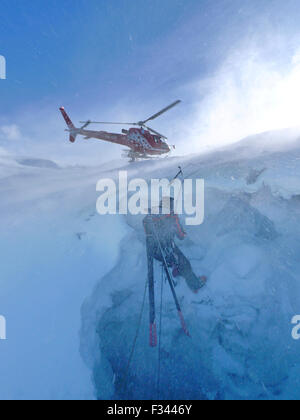 A mountain rescue technician is descending into a crevasse. When an off piste skier breaks through the snow and - Stock Photo