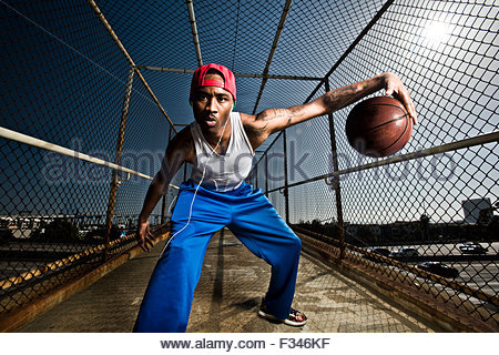 A young man playing around with a basketball. - Stock Photo