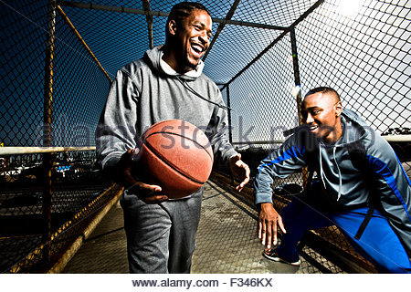 Two friends play around with a basketball - Stock Photo