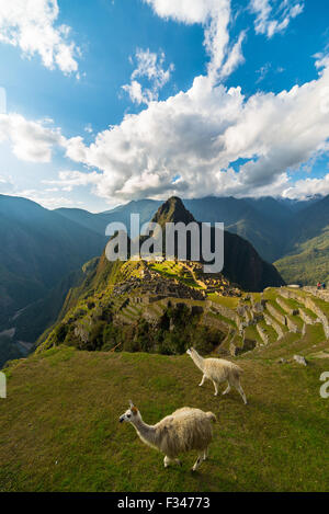 Machu Picchu illuminated by the last sunlight coming out from the opening clouds. Wide angle view from above with - Stock Photo