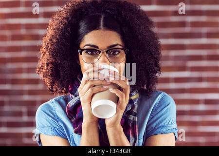 Attractive hipster drinking out of take-away cup - Stock Photo