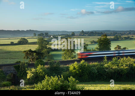 the London Waterloo to Exeter train passing Milborne Wick on a misty summer's morning, Somerset, England, UK - Stock Photo