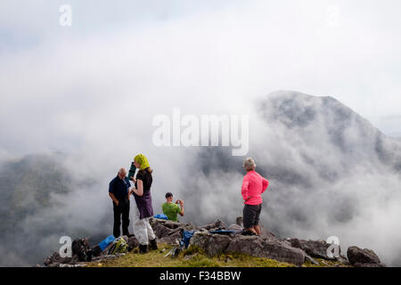 Hikers resting on Beenkeragh looking at view to Carrauntoohil through low cloud in MacGillycuddy Reeks County Kerry - Stock Photo