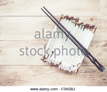 Empty plate and chopsticks on wooden table - Stock Photo