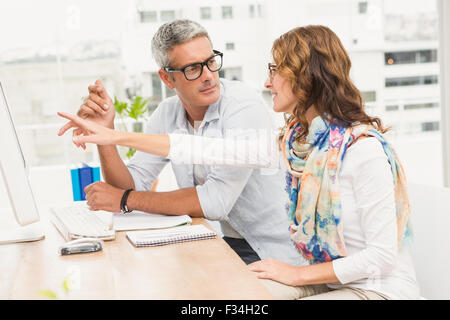 Two casual designers discussing and working with computer