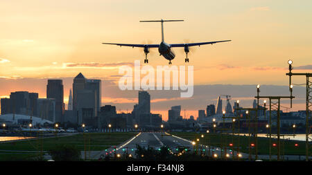 FlyBe Dash8 landing at London City Airport at sunset - Stock Photo