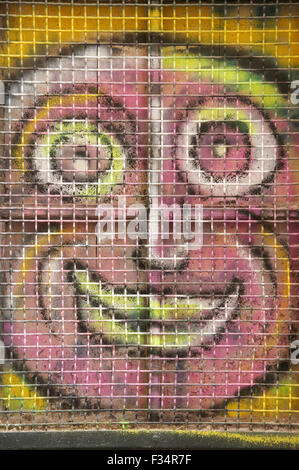 Ugly pink face. Colourful graffiti spray painted on a window shutter. Detail of urban street art by artist known as Loko. Montpellier, South of France.