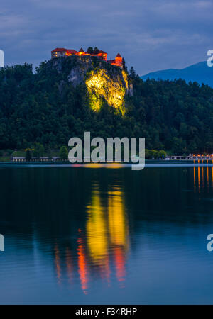 Illuminated Bled Castle at Bled Lake in Slovenia at Night Reflected on Water Surface - Stock Photo
