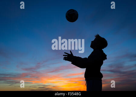 silhouette of a boy playing outside at dusk - Stock Photo