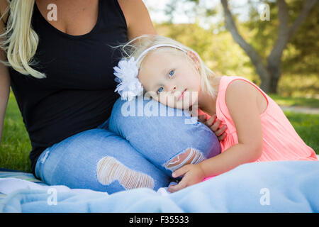 Beautiful Young Blue Eyed Girl Resting on Her Mommy's Lap Outside At the Park. - Stock Photo