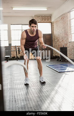 Man exercising with battling rope - Stock Photo