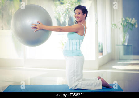 Portrait of pregnant woman holding exercise ball - Stock Photo