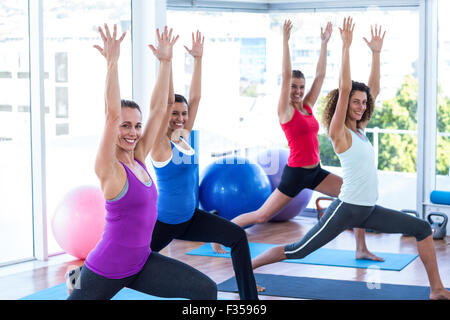Cheerful women doing low warrior pose in fitness studio - Stock Photo
