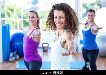 Fit women doing warrior II pose in fitness studio - Stock Photo