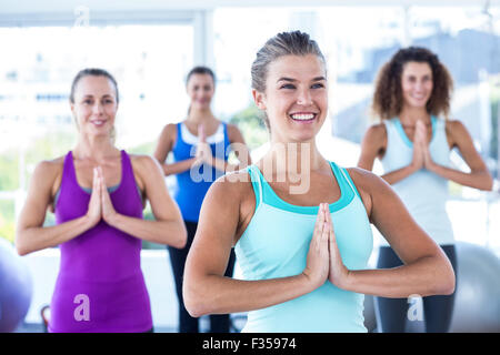 Happy women with hands together in fitness studio - Stock Photo