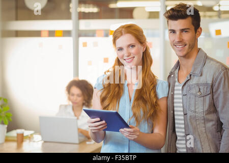 Portrait of business people holding digital PC - Stock Photo