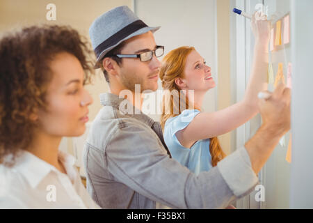 Business people writing on adhesive notes on glass wall - Stock Photo