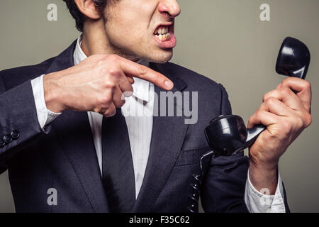 An angry young businessman is on the phone and screaming - Stock Photo