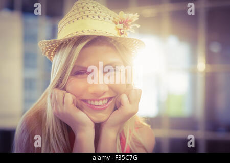 Portrait of happy businesswoman wearing hat - Stock Photo
