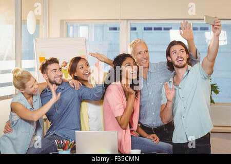 Business people taking selfie in meeting room - Stock Photo