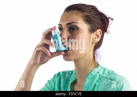 Close-up of woman using asthma inhaler - Stock Photo