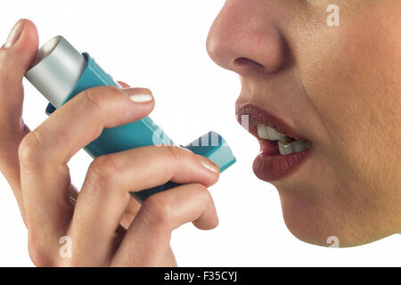 Close-up of woman face while using asthma inhaler - Stock Photo
