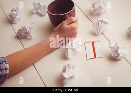 Hands holding coffee cup next to paper balls and sticky note - Stock Photo
