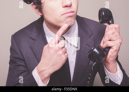 Young businessman is on the phone and is thinking about what to say - Stock Photo