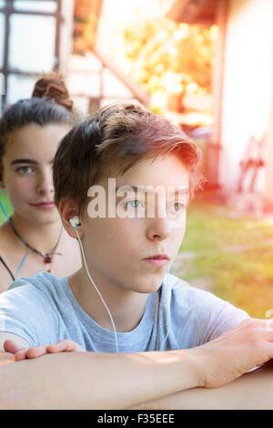 teenage boy hears music, a second behind him - Stock Photo
